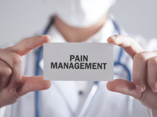 Physical therapist holding a card that says pain management
